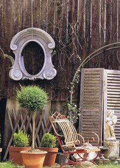 French decor in garden - love the combination of the worn wood and rusty chair with concrete statue and terra cotta.  This is so beautiful to look at.