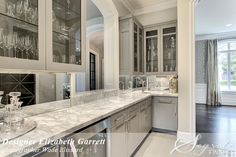 Huge butlers pantry with cabinetry in high-gloss Sherwin Williams Dovetail, marble counters and antique mirrors by Elizabeth Garrett DeWitt.