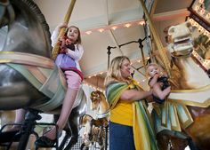 Stacey Griffin, center, and children Katherine, 8, and Nathan, 1, enjoy a ride on the Hampton Carousel on Monday afternoon. (Photo by Kaitlin McKeown/Daily Press)