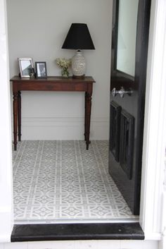 Tiles from Jatana Interiors, love the black door with the grey tiles and white walls. So simple but so stylish