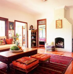 Beautiful Moroccan style living room. Lush kilim rug & raised poufs. Fresh white base and gorgeous carved timber ornate door feature overhead.