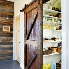 Reclaimed barnwood walls and a rolling barn door pantry redefines a kitchens look. This brings in multiple soft colors without painting and adds to texture.