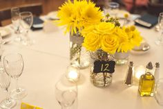 Simple centerpieces of bright yellow flowers in glass jars with navy-and-white-striped ribbon Wedding Ceremony and Reception Venue: Salvatore's Ristorante   Wedding Photographer: Jessica Eileen Drogosz Photography  Wedding Florist: Fleur De Lis