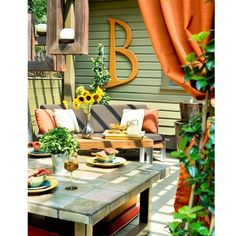 Colorful backyard patio space - Love the initial on the wall!