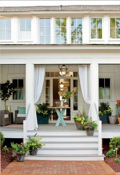 Porch Design Ideas. This porch decor is perfect for summer. Let's spend time outdoors!Classic wall-mounted and hanging lanterns by New Orleans-based Bevolo surround the home with historical charm.  Outdoor curtains give this porch the feel of a finished room. #Porch #PatioDecor #Summer