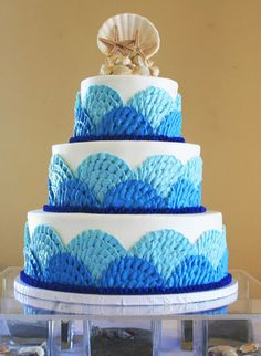 Buttercream waves and a beautiful seashell and starfish cake topper, by Freedom Bakery and Confections.
