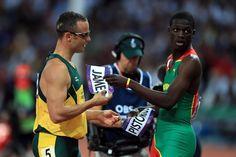 Oscar Pistorius and Kirani James exchanging name bibs.