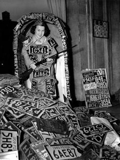 Mae Peister, with rifle in hand, pretends to guard the collection of old automobile license plates at the Keystone Auto Club in Philadelphia, Pa., April 11, 1942. The plates will be recycled into metal for the war effort ~