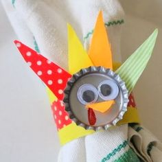 The perfect napkin ring for your Thanksgiving kids' table.  Grab some bottle caps and paper towel rolls and make this recycled craft.
