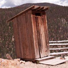 An outhouse balances precariously on the edge of a cliff.