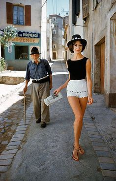 Irène Gindry in white shorts by Angelo walking down a narrow street in St. Tropez, photo by Mark Shaw, 1961
