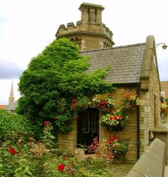lovely stone home, love all of the flowers