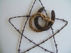 """BARBED WIRE STAR W/ROPE HORSESHOE: Rusty barbed wire star is 13"""" across. The rope and horseshoes are wired in place. Great wall decor. i see a DIY"""