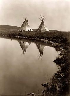 Two tepees reflected in water of pond, with four Piegan Indians seated in front of one tepee - Edward S. Curtis 1910