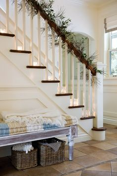 """Tealight holders placed on the edge of the stair's treads draw attention to the staircase and the subtle festive decoration made of olive branches. A cosy throw and bench are a welcoming touch for those coming in from the cold."""