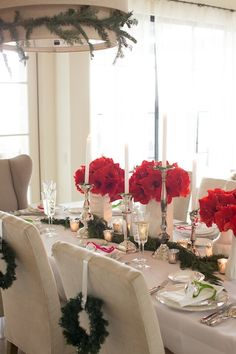 #Christmas brunch #tablescape. White is always perfect for each occasion! Love that #centerpieces with red flowers and #candles! Nice detail: #wreaths behind the chairs