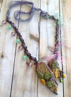 BV October Challenge .. BoHo Heart Necklace .. Heart is made with Polymer Clay, a B'sue stamping was cut into several pieces and implanted into clay, spectra beads and brass chain hang from one side of the heart. Neck chain is brass with B'sue Silk Ribbon woven into chain and on the other side I used yarn .. Green and Purple glass beads also used .. Designed by Jann Tague .. Clever Designs .. https://www.facebook.com/JewelsByJann