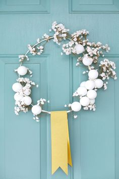 White winter wreath with a coat hanger and ping pong balls!