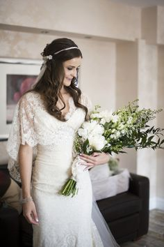 Relaxed over the arm bouquet with white Peonies and Larkspur. Love the dress.