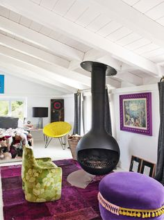 Escape to the Coolest Coastal Home in Spain // Fireplace and purple accents