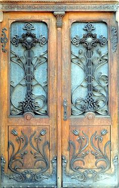 Scrollwork wrought iron on weathered wooden doors with frosted glass... beautiful!