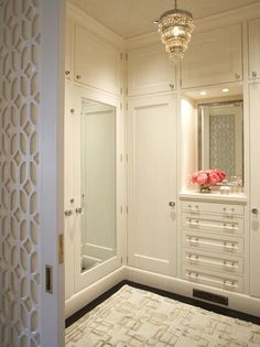 Glamorous closet with vintage crystal chandelier and mirrored doors by Massucco Warner Miller Interior Design #chandelier #closet #dressing_room #glam #mirror