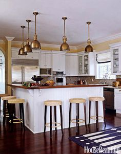 A nautical theme drove the kitchen design. Brass pendants from Circa Lighting hang above a beaded board island with a waxed teak top. Design: Bill Brockschmidt and Courtney Coleman