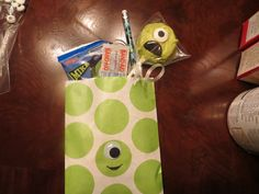 Monsters University Birthday Goodie Bag-glued large eyeball to a polka-dot paper bag from Party City and filled with Oreo Pop, Fruit Snacks, Pencils, and MU Bandaids & Tattoos!  Easy!