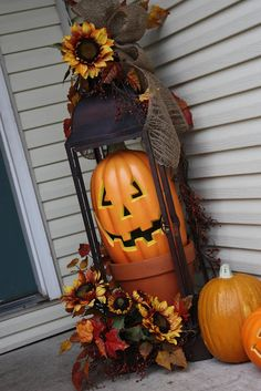 DIY Halloween Front porch decor inspiration - love this idea with the tall lantern and faux pumpkin and flowers holiday, halloween decorations, falldecor, pumpkins, fall decorating, jack o lanterns, fall porches, clay pots, front porches