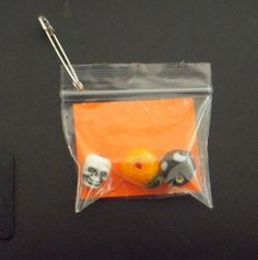 """This is an easy SWAP that uses bulk halloween themed beads: a skull, a pumpkin and a black cat. The orange card reads """"Halloween in a Bag"""" and has the girl's name and troop number on back."""