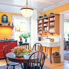 """""""The look is low-key Victorian,"""" says home-owner and architect Sandy Vitzthum, who mixed timeworn furniture, such as a distressed table, with more refined turn-of-the-century touches, like a pendant lamp. A cast-iron sink and prized cherry-red Aga stove add extra character and do double duty as prep surfaces. 