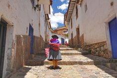 Quichua woman slowly makes her way up steep narrow streets in the San Blas neighborhood of Cusco, Peru