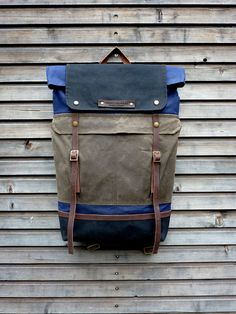 Waxed canvas backpack / rucksack with folded top and waxed canvas shoulderstrap and bottom on Etsy.