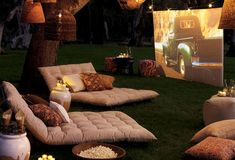 Outdoor movie lounge with cushions. pillows and an outdoor screen