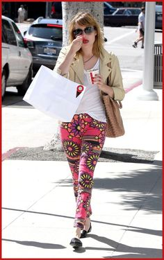 Emma Roberts wearing a colourful pink floral jeans paired with a casual white T-shirt, beige leather jacket as she picked up some ice cream in Beverly Hills.