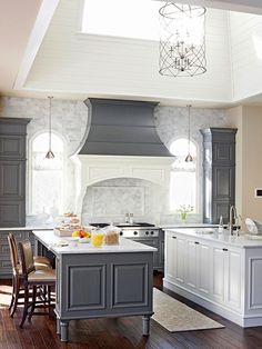 Things I love about this kitchen: beautiful gray stone walls, a skylight for extra light, two islands, and a cool color palette.