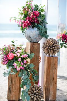 Lush flowers, wooden pillars and shell vases create a natural, seaside vibe.  Design by Alchemy Fine Events