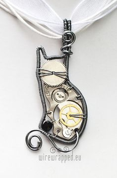 "Grey Steampunk Cat Wirewrapped  Pendant...    The main part of this kitten pendant comes from a vintage watch. The small bead is fire polished glass. The wire is grey enamel plated copper.    ~Measures about 4.5cm (1.8"")  ~Comes with a clasped ribbon"