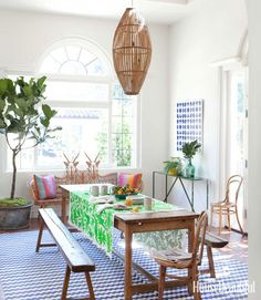 This boho dining room has charm galore with a simple long wood dining table and mismatched chairs accented by bright linens and rattan light fixture.