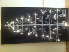 DIY chalkboard panel Christmas tree with holes punched for lights!  Awesome.