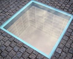 """Monument to the May 10, 1933 Book burning: Designed by Micha Ullmann, empty bookshelves, enough to hold all 20,000 burned books, visible below the pavement of Bebelplatz in Berlin, Germany. Besides the glass plate there are two bronze plaques, including a memorable quote from Heinrich Heine's play Almansor:  """"Where one burns books, it is only a prelude; in the end one also burns people"""" circa 1820."""