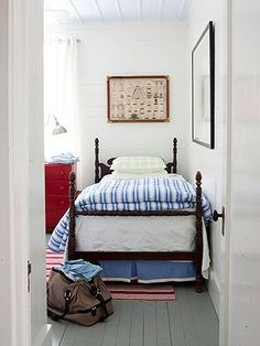 Whitewashed walls and horizontal planks create a relaxing backdrop in the second bedroom. Vintage nautical accessories decorate the room. The red, white, and blue color scheme accentuates these pieces.