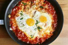 Shakshuka is an Israeli dish of eggs poached in a spicy tomato sauce and often served with Haloumi or Feta cheese inside. A delicious and healthy breakfast that can really be eaten at any time. #recipes #israelirecipes #jewishrecipes #israelifood
