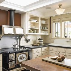 Salvaged stove: The refinished shell of an antique wood-burning range encases a new glass cooktop. A black stovepipe masks the ducting that leads to a vent fan in the attic.