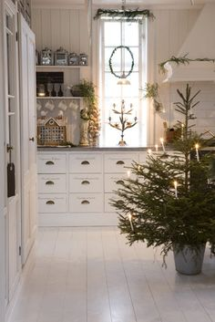 love the scroll writing on the drawers, and the way the greenery pops holiday, christmas kitchen, christmas decorations, white christmas, swedish style, scandinavian christmas, drawer, christmas trees, white kitchens