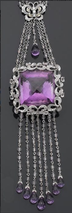 An amethyst, diamond, and gem-set necklace.  featuring a square briolette-shaped amethyst, within an openwork frame, suspended from a triple-link chain of butterfly motif, completed by fringe, set throughout with round brilliant-cut diamonds, bead and oval-shaped rose quartz, circular-cut yellow sapphires, and briolette-shaped amethysts; estimated total diamond weight: 1.75 carats; mounted in eighteen karat white gold; length: 25½in.