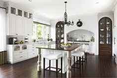 Kitchen :: Mediterranean style kitchen with kitchen stove alcove with French range, built-in spice nooks Kitchen cabinets with glass front drawers and coffee station. Arched mahogany glass-front cabinets fill alcoves beside stove. :: Caden Design Group