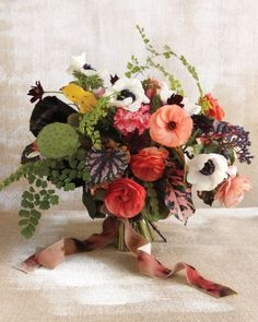 Using houseplants in arrangements - Ranunculus, anemones, chocolate cosmos, lotus pods, and viburnum berries, this is strangely pretty to me, and brings in some of the chartreuse green and then the paler coral colors too.