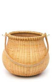 """Nantucket Pot Belly Basket  6"""" x 5"""" w/o handle    This basket was woven over a 5-part puzzle mold by Jim Rutherford. The challenge of this basket, besides getting the mold out, is the complicated double taper on the staves. They need to not only be tapered on to the base, but also to the top of the basket. This basket is woven of cane on cane with an oak base and handle."""