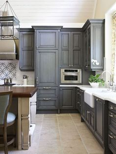 charcoal gray kitchen cabinets with calcutta marble counter tops, farmhouse sink, white & gray mosaic tiles backslash, subway tiles, backslash, white washed, kitchen island, butcher block counter top, yellow walls paint color and kitchen island lanterns.